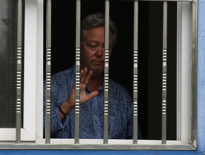 Chip Starnes, the co-owner of Coral Springs, gestures to journalists from a window as he is held hostage by workers inside his plant, on the