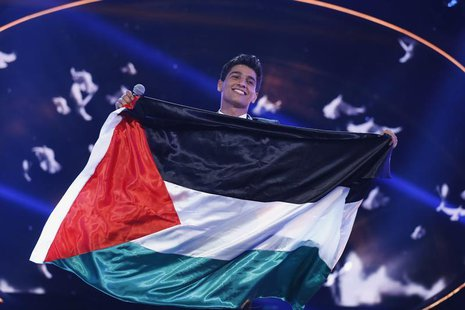 Palestinian singer Mohammed Assaf holds the Palestinian flag, as he stands on stage after being announced winner during the Season 2 finale