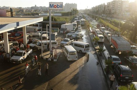 Drivers wait alongside their vehicles in long queues at a gas station during a fuel shortage in the country, in Alexandria June 24, 2013. RE