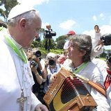 Pope Francis (L) greets musicians as he welcomes more than 250 children who arrived after travelling by train from Milan at the St. Peter tr