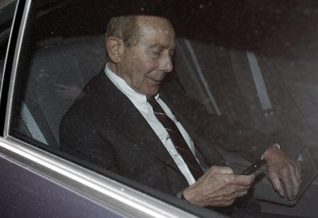 "Former CEO of American International Group Inc, Maurice ""Hank"" Greenberg, checks his phone inside a car after leaving a building in downtown"