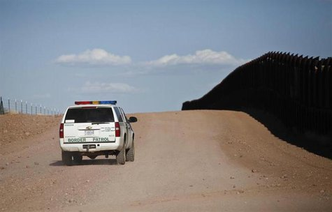U.S. Border Patrol surveys the border fence near rancher John Ladd's property adjacent to the Arizona-Mexico border near Naco, Arizona, Marc