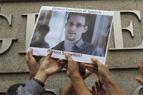 Protesters in support of Edward Snowden, a contractor at the National Security Agency (NSA), hold a photo of him during a demonstration outs