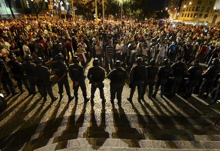 Demonstrators gather during a protest as police officers stand guard in central Rio de Janeiro June 24, 2013. REUTERS/Lucas Landau
