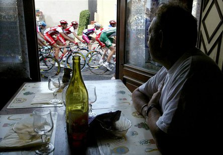 A man in a cafe looks out of the window at a pack of riders making their way through the 230-km (143-mile) sixth stage of the Tour de France