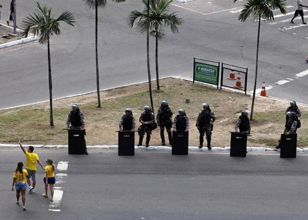 Soccer fans walk past members of a Brazilian special anti-riot unit at a security checkpoint outside the stadium before the Confederations C