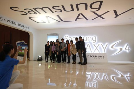 Visitors take a group photo next to a logo of Samsung Electronics Co Ltd's latest flagship smartphone S4 during its launch event at the comp