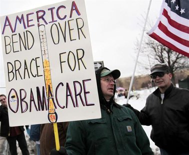 "A Tea Party member carries a sign voicing his concern over ""ObamaCare"" during a rally marking the one-year anniversary of the movement in Tr"