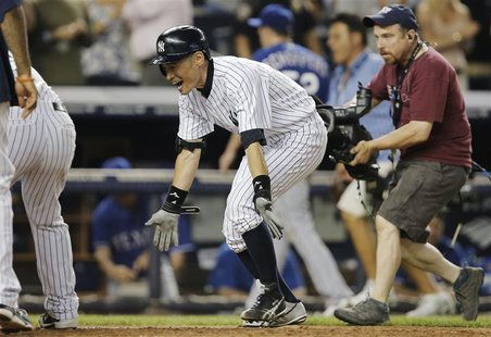 New York Yankees batter Ichiro Suzuki (C) spreads his arms as he runs past Texas Rangers relief pitcher Tanner Scheppers (3rd R, rear) to te