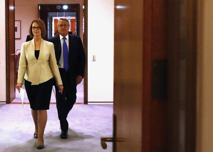 Australian Prime Minister Julia Gillard (L) walks into the Cabinet Room with Treasurer Wayne Swan at Parliament House in Canberra May 13, 20