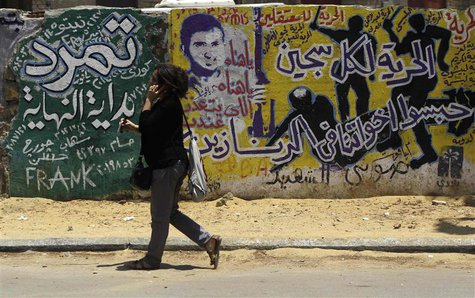 A woman walks past graffiti depicting riot police near Tahrir Square in Cairo June 23, 2013. REUTERS/Amr Abdallah Dalsh