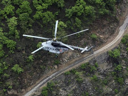 An Indian Air Force (IAF) helicopter, part of a rescue operation, flies over the Gauchar area after heavy rains in the Himalayan state of Ut