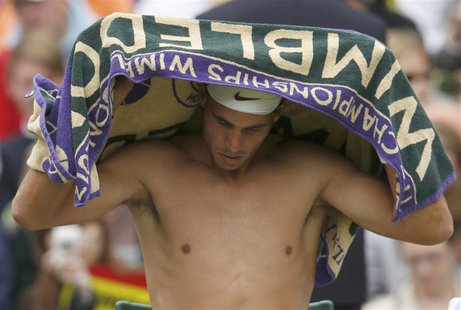 Rafael Nadal of Spain wipes himself with a towel during his men's singles tennis match against Steve Darcis of Belgium at the Wimbledon Tenn
