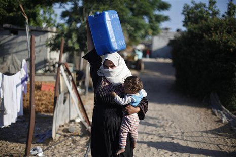 A Palestinian woman carries her daughter as she makes her way to fill a container with water from a nearby tank in Khan Younis in the southe