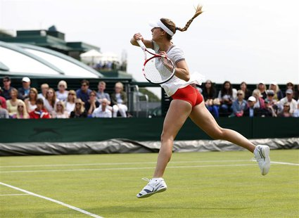 Alize Cornet of France hits a return to Hsieh Su-Wei of Taiwan in their women's singles tennis match at the Wimbledon Tennis Championships,