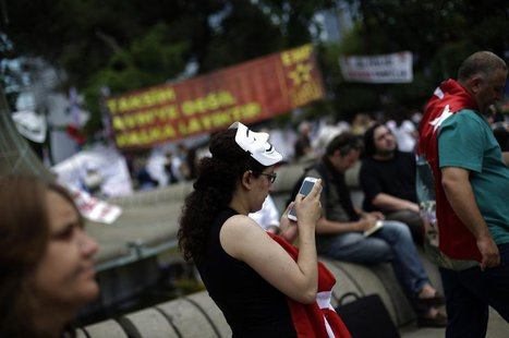 A protester uses her mobile device as she walks at Gezi Park on Taksim Square in Istanbul June 6, 2013. REUTERS/Stoyan Nenov