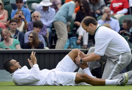 Jo-Wilfried Tsonga of France receives treatment during his men's singles tennis match against Ernests Gulbis of Latvia at the Wimbledon Tenn