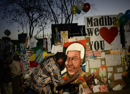 A man paints a portrait of ailing former South African President Nelson Mandela outside the Medi-Clinic Heart Hospital where he is being tre