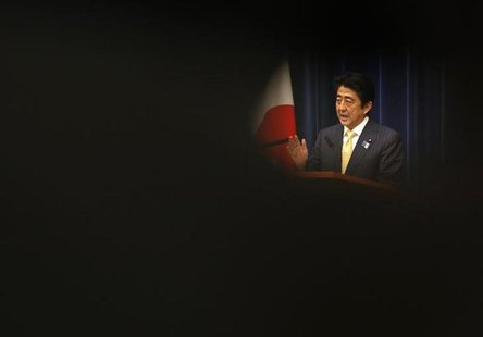 Japan's Prime Minister Shinzo Abe is seen through reporters as he speaks during a news conference at his official residence in Tokyo June 26