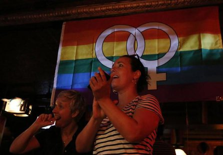 Patrons watch coverage of the U.S. Supreme Court ruling on the Defense of Marriage Act at the Stonewall Inn in New York June 26, 2013. REUTE