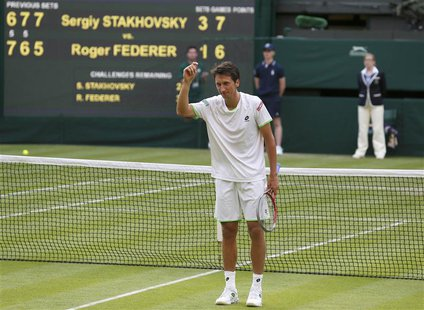 Sergiy Stakhovsky of Ukraine reacts after defeating Roger Federer of Switzerland in their men's singles tennis match at the Wimbledon Tennis
