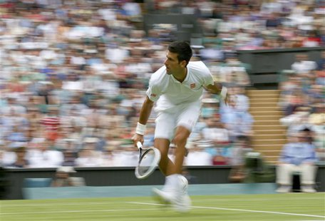 Novak Djokovic of Serbia hits a return to Florian Mayer of Germany in their men's singles tennis match at the Wimbledon Tennis Championships