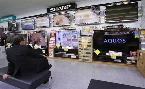 A man looks at Sharp Corp's Aquos television sets displayed at an electronics store in Tokyo January 15, 2013 file photo. REUTERS/Toru Hanai
