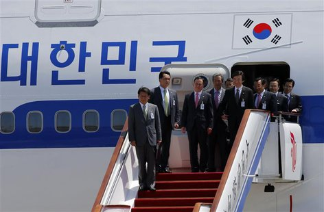 South Korean government officials and lawmakers accompanying President Park Geun-hye (unseen) arrive at the airport in Beijing June 27, 2013