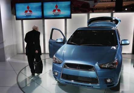 A journalist inspects the 2011 Mitsubishi Outlander sport compact SUV at the New York International Auto Show in New York April 1, 2010. REU