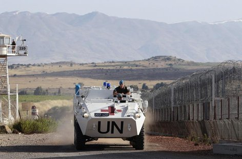 United Nations (U.N.) peacekeeping soldiers from Austria drive past an observation tower near the Quneitra border crossing between Israel an