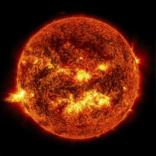 The bright light of a solar flare on the left side of the sun and an eruption of solar material shooting through the sun's atmosphere, calle
