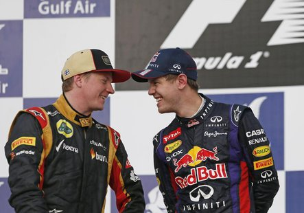 Lotus Formula One driver Kimi Raikkonen of Finland shares a laugh with Red Bull Formula One driver Sebastian Vettel (R) of Germany after the