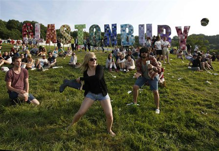 Festival goers play baseball, batting a beer can with a wellington boot, on the first day of Glastonbury music festival at Worthy Farm in So