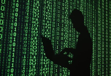 An illustration picture shows a projection of binary code around the shadow of a man holding a laptop computer in an office in Warsaw June 2