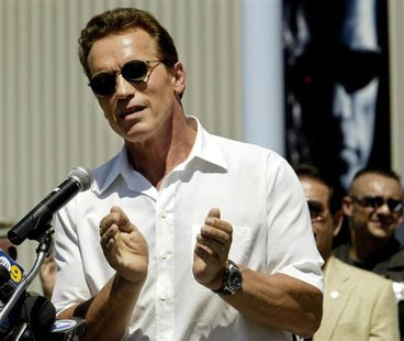 "With a poster from his latest film ""Terminator 3"" in the background, actor Arnold Schwarzenegger applauds youths in attendance at opening ce"