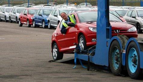 A worker loads a car onto a transporter at the PSA Peugeot Citroen Ryton plant in Coventry, central England, April 18, 2006. REUTERS/Darren
