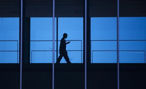 A student uses his mobile phone as he walks inside the Engineering building at the University of Waterloo, located beside the Blackberry mak