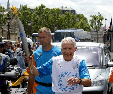 Former French Athletism champion Alain Mimoun holds the Olympic Flame during Day 21 of the Athens 2004 Olympic Torch Relay, June 25, 2004 in