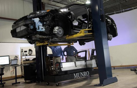 Team members raise a Chevrolet Volt electric vehicle on a hoist after releasing the battery from the underside at a design studio in Troy, M