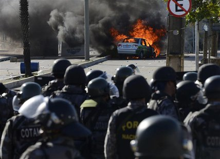 A vehicle is set on fire near riot policemen during a protest near the Estadio Castelao, where the Confederations Cup semi-final match betwe