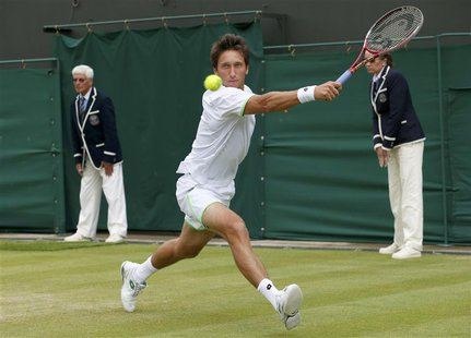 Sergiy Stakhovsky of Ukraine hits a return to Jurgen Melzer of Austria during their men's singles tennis match at the Wimbledon Tennis Champ