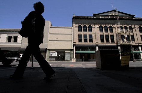 A woman walks past shuttered businesses in Stockton, California June 27, 2012. REUTERS/Kevin Bartram