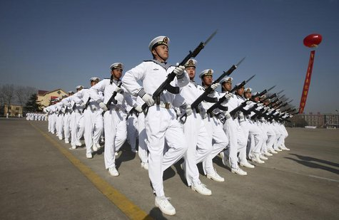 New recruits of the Chinese Navy march with their guns during the parade marking the end of their first training session in Qingdao, Shandon