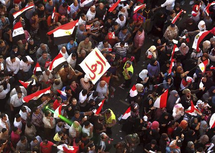 "Protesters, with flags and a banner reading ""Leave"", chant anti-President Mohamed Mursi slogans during a protest in Tahrir square in Cairo J"