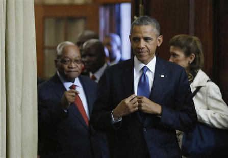 U.S. President Barack Obama (C) arrives at a joint news conference with South Africa's President Jacob Zuma (L) at the Union Buildings in Pr