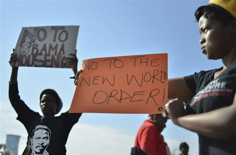 Protesters hold placards outside the University of Johannesburg in Soweto, ahead of a visit by U.S. President Barack Obama, June 29, 2013. R