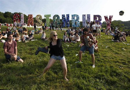 Festival goers play rounders with a wellington boot and a beer can on the first day of Glastonbury music festival at Worthy Farm in Somerset
