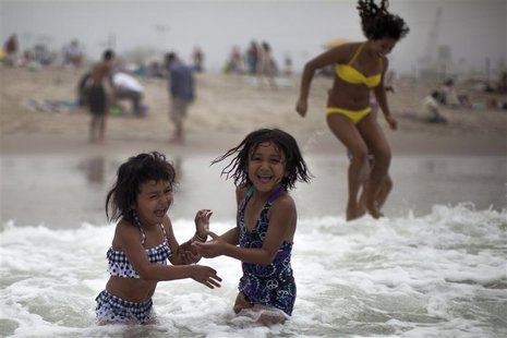 Celeste Hidalgo, 7, (R) and Alana Griego, 5, cool off in the Pacific ocean during a heat wave in Santa Monica, California, June 28, 2013. RE
