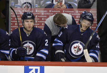 Winnipeg Jets' Tobias Enstrom (R) is attended to on the bench after being injured against the Buffalo Sabres during the first period of thei