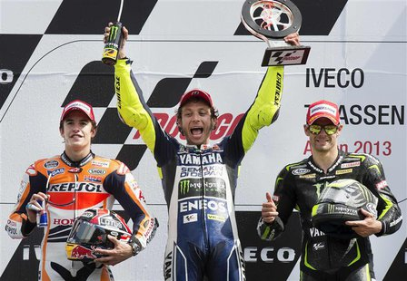 Yamaha MotoGP riders Cal Crutchlow of Britain and Valentino Rossi of Italy (C), and Honda MotoGP rider Marc Marquez of Spain (L) celebrate o